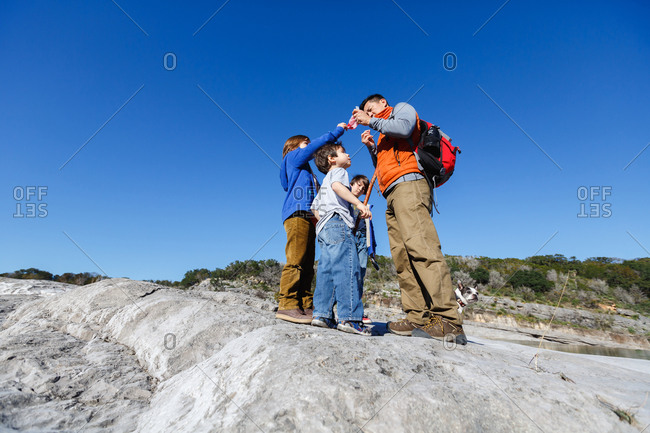 Father and sons standing together on a hike