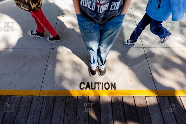Feet of three children near a caution sign