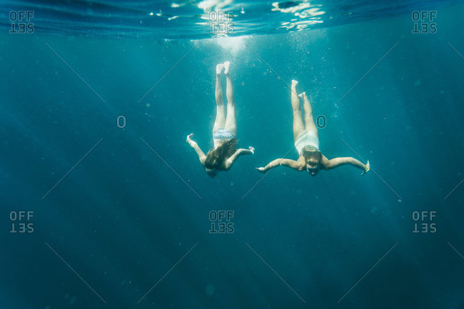 Two women diving under the sea