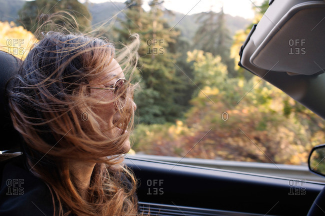 Smiling woman driving open top car