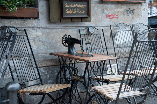 Krakow, Poland - May 28, 2011: Chairs and an old-fashioned sewing machine on a sidewalk in Krakow, Poland