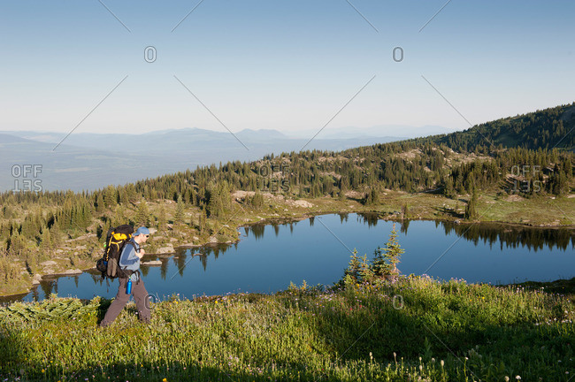 Hiker on a green mountain ridge overlooking a lake