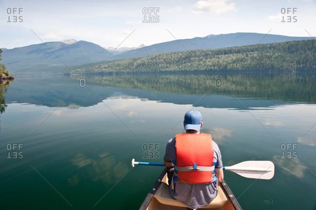 Paddler in a canoe on a pristine wilderness lake in the mountains