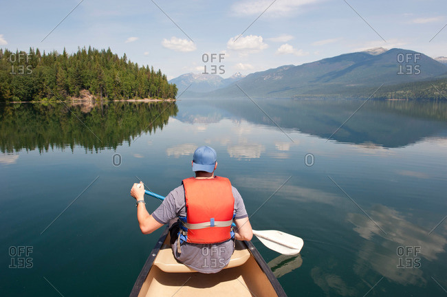 Man paddling a canoe on a pristine wilderness lake in the mountains