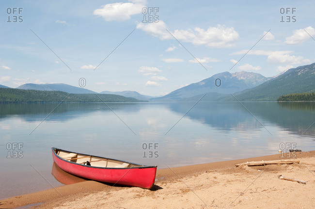 Canoe on a sandy beach at a pristine wilderness lake in the mountains