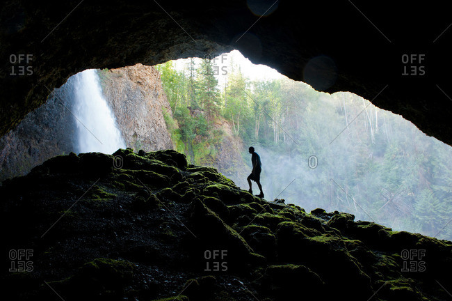 Man hiking near the mouth of a cavern at a waterfall