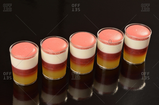 A row of colorful verrines on a glossy table