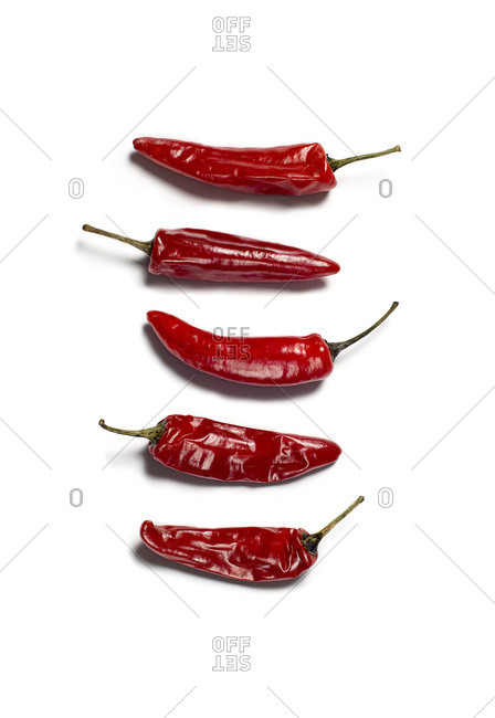 A stack of five red hot peppers