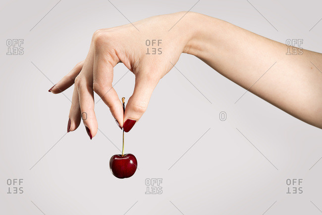 Woman's hand with red painted nails holding a bright red cherry by the stem