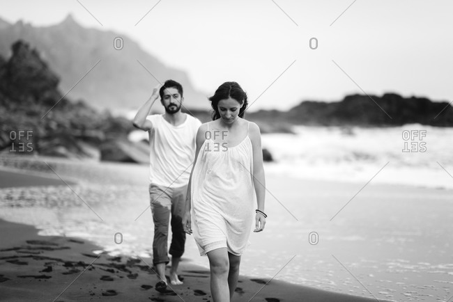 Man following his partner as they walk on beach