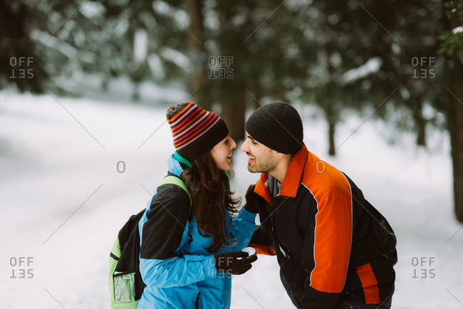 Woman holds engagement ring after her fiance just proposed in the snowy woods