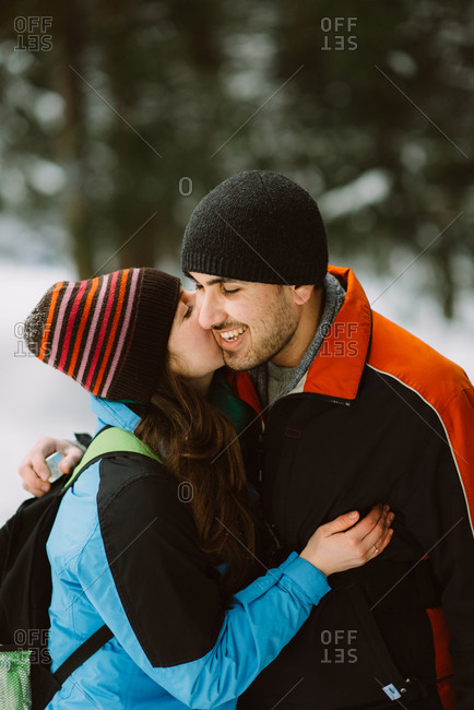 Woman kissing her fiance in snowy woods