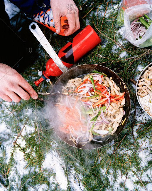 Person cooking on a wok outdoors, Harjedalen, Sweden