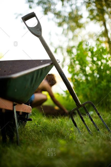 Pitch fork against a wheelbarrow in garden, Sweden