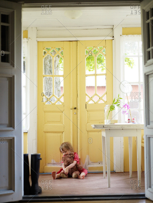 Girl with a teddy bear by a outer door