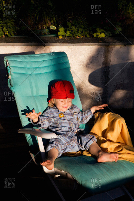 Boy in a lounger blinded by the sun
