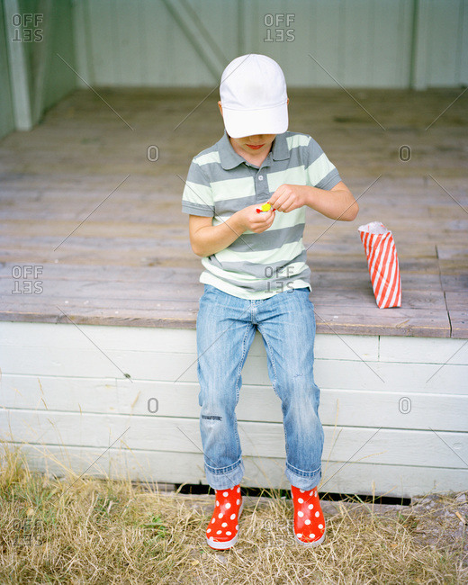 Boy in a cap eating candy