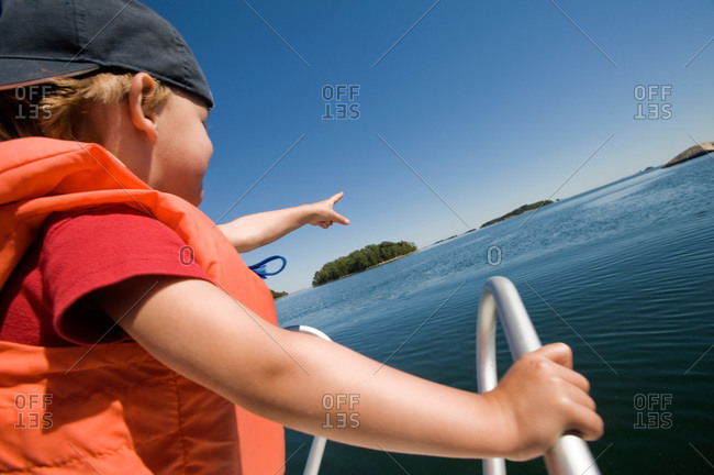 Boy in a motorboat pointing