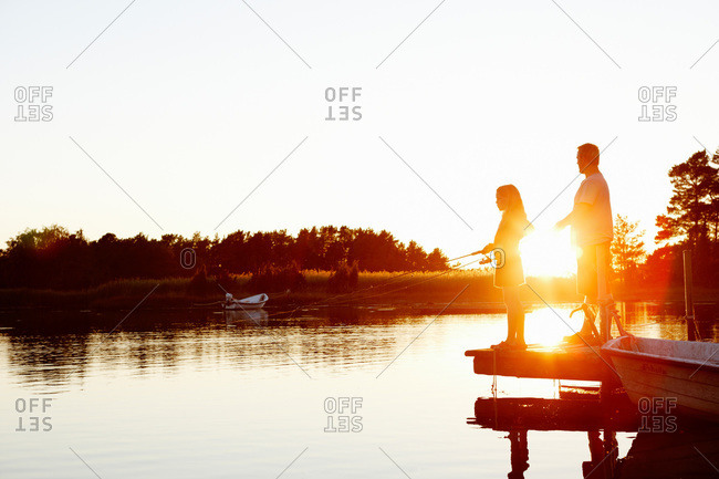 Father and daughter fishing at sunset