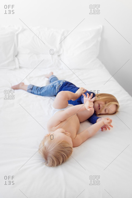 Brother and sister wrestling on a white bed