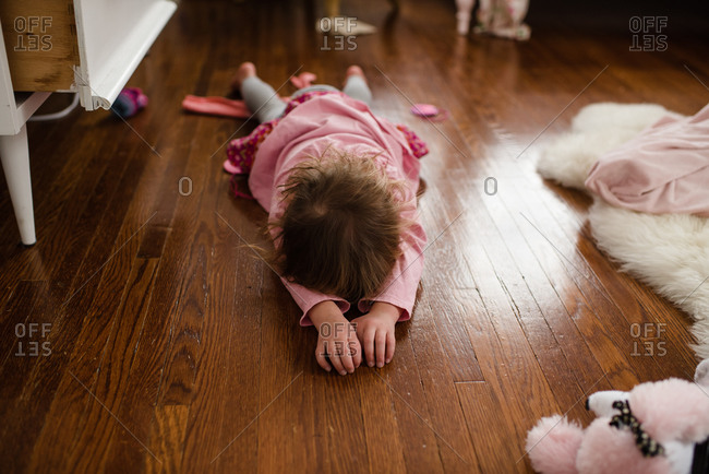 Little girl lying face down on the hardwood floor