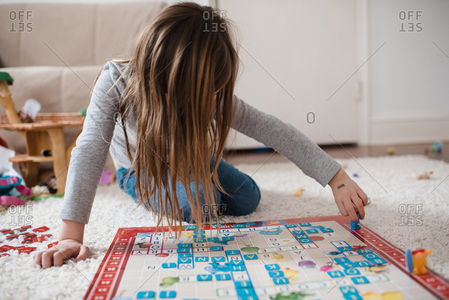 Little girl playing a board game stock photo - OFFSET