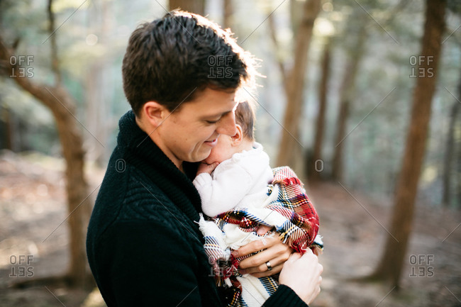 Father holding baby son wrapped in blanket in woods