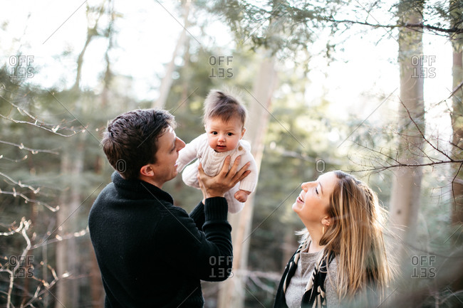 Adoring new parents gaze at their cute baby in the woods
