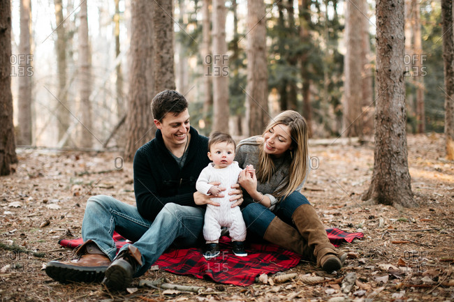 Two young parents sitting on plaid blanket in woods with their cute baby boy