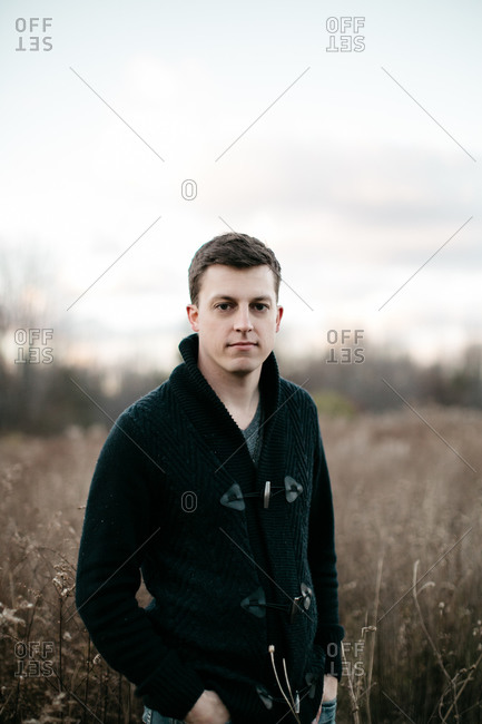 Portrait of handsome man in cable knit cardigan standing in field in autumn