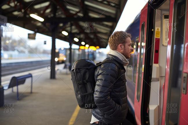 Man Standing On Railway Platform Waiting To Board Train