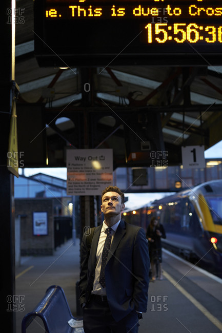 Businessman Stands On Platform Looking At Train Schedule Display
