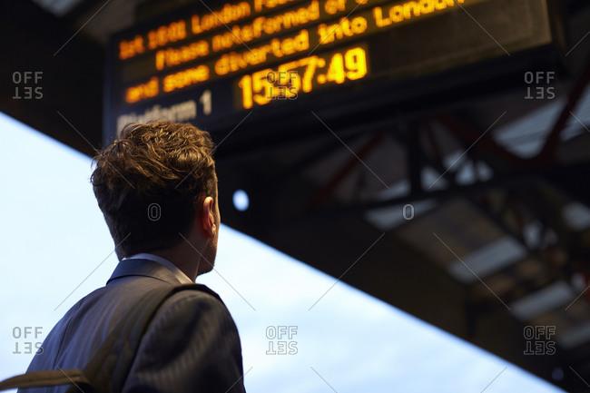 Man Looking At Train Schedule Display