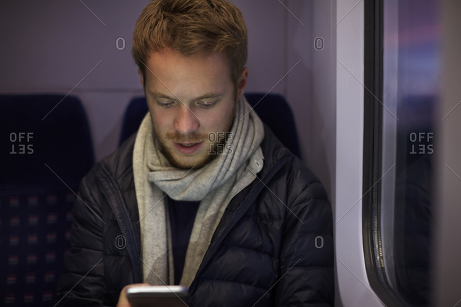 Man Sitting In Train Carriage Sending Text Message