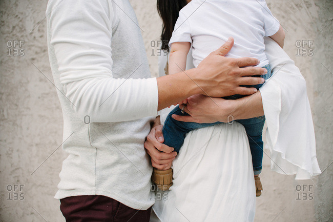 Midsection of couple holding baby