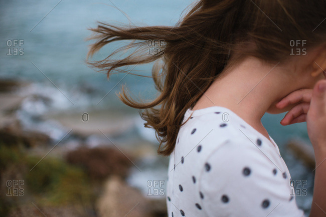 Wind blown of girl by coast