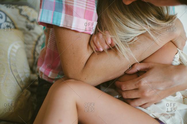 Mom holding girl close