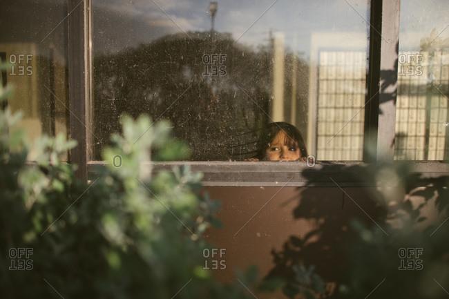 Girl peeking out a window
