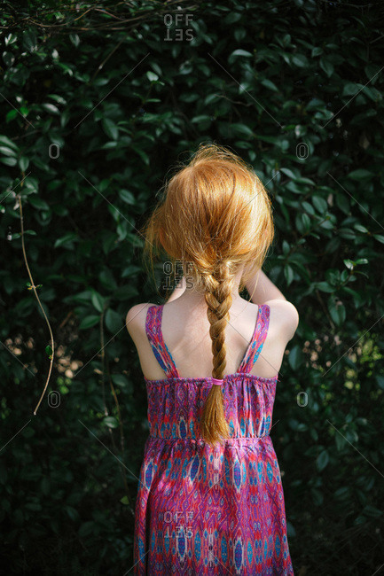 Redhead girl with braid by hedge