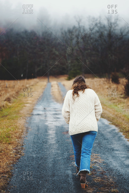 Woman walking down a gravel road