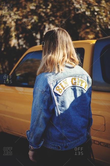 Woman in jean jacket by truck