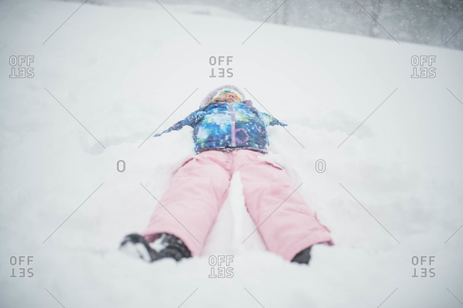 Young girl lying on her back in snow