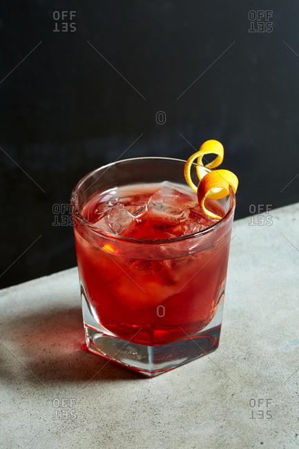 Red cocktail on a table with an orange garnish
