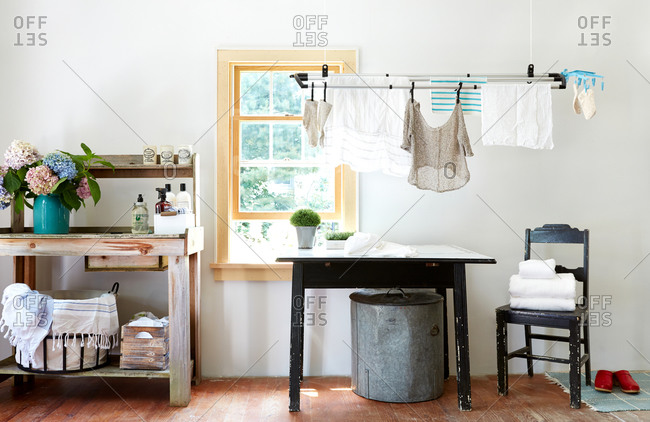 Laundry hanging up to dry in front of a window in a brightly lit room