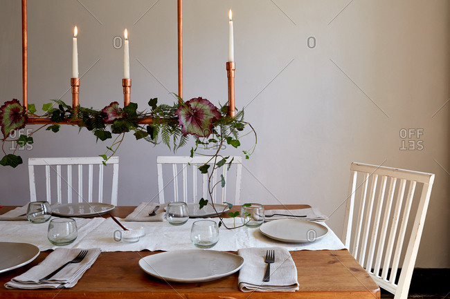 Wood farm table with place settings framed by a copper chandelier