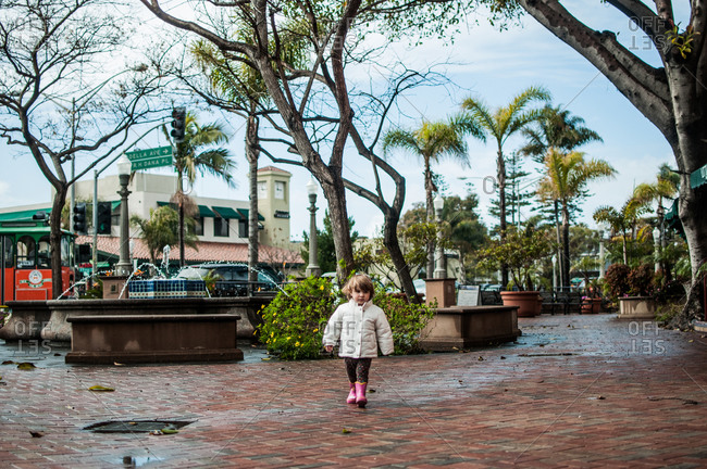 Toddler girl walking in a brick plaza