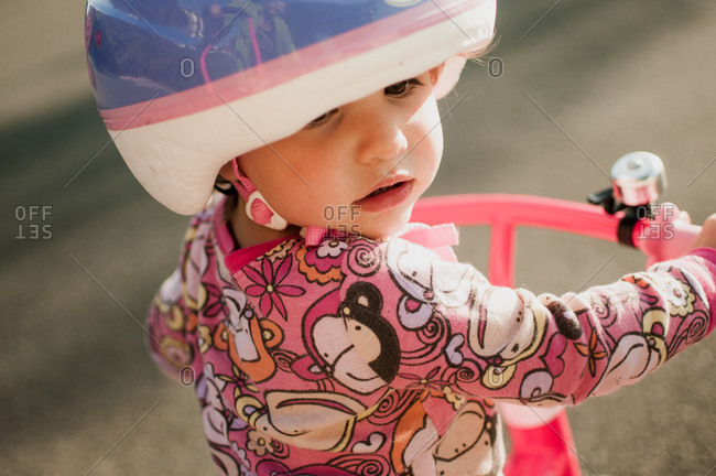 Girl in a pink and purple bicycle helmet