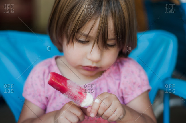 Little girl in a folding chair eating a popsicle