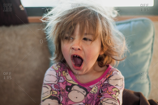 Little girl with bedhead yawning