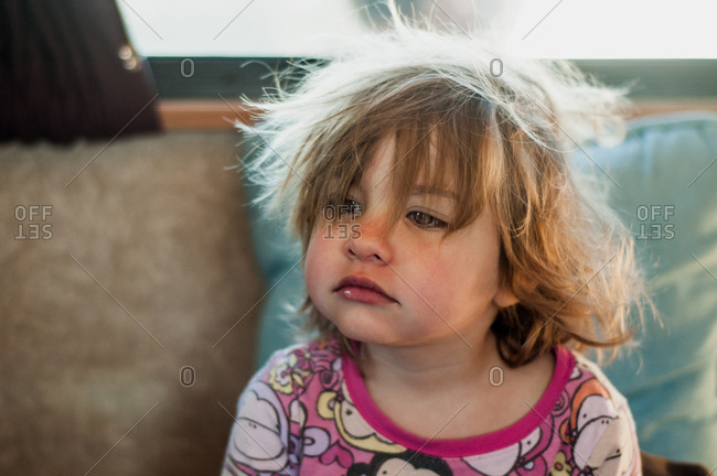 Sleepy little girl with bedhead sitting on a sofa